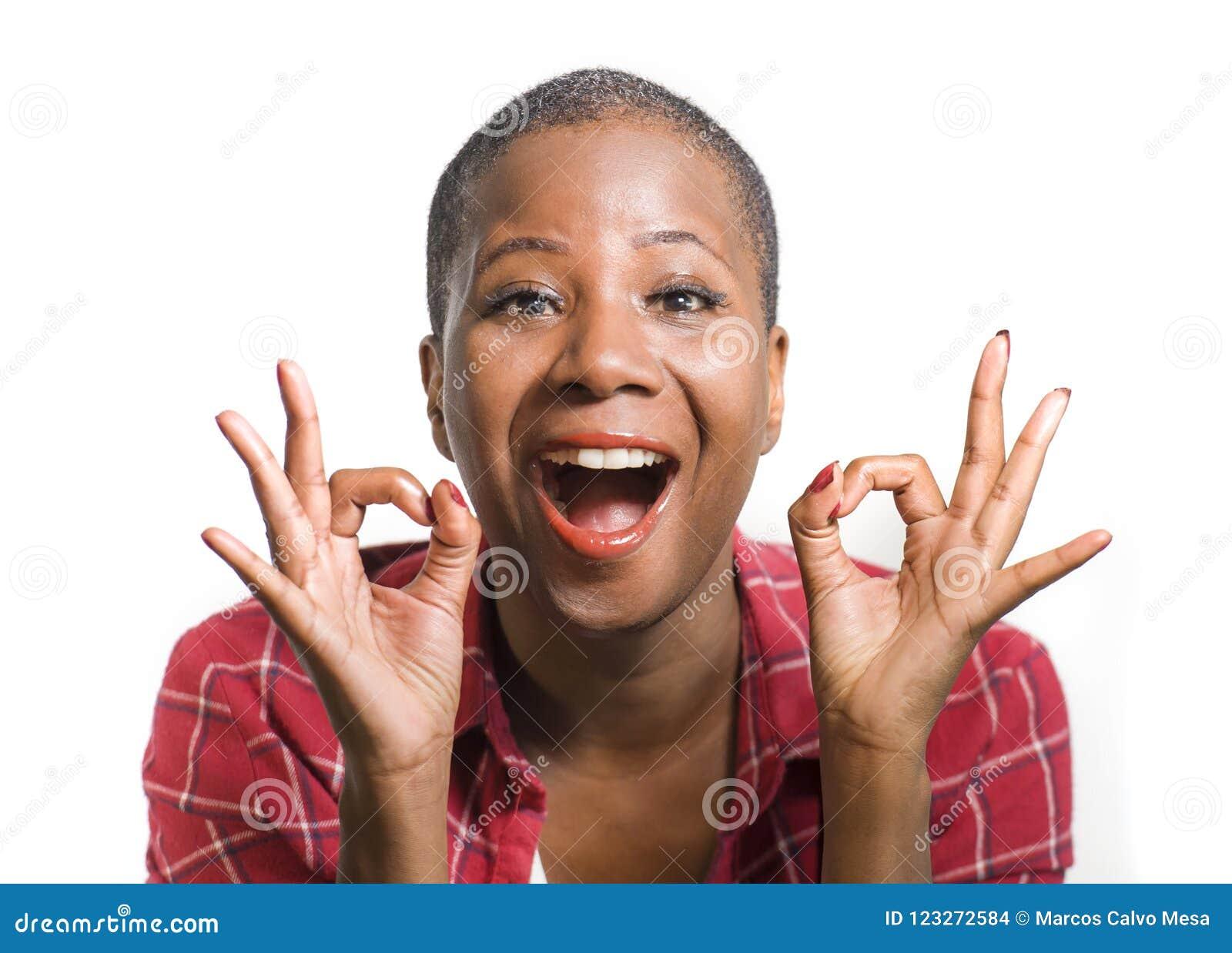 O estilo de vida isolou o retrato da mulher afro-americana preta atrativa e natural nova que gesticula o sucesso de comemoração f