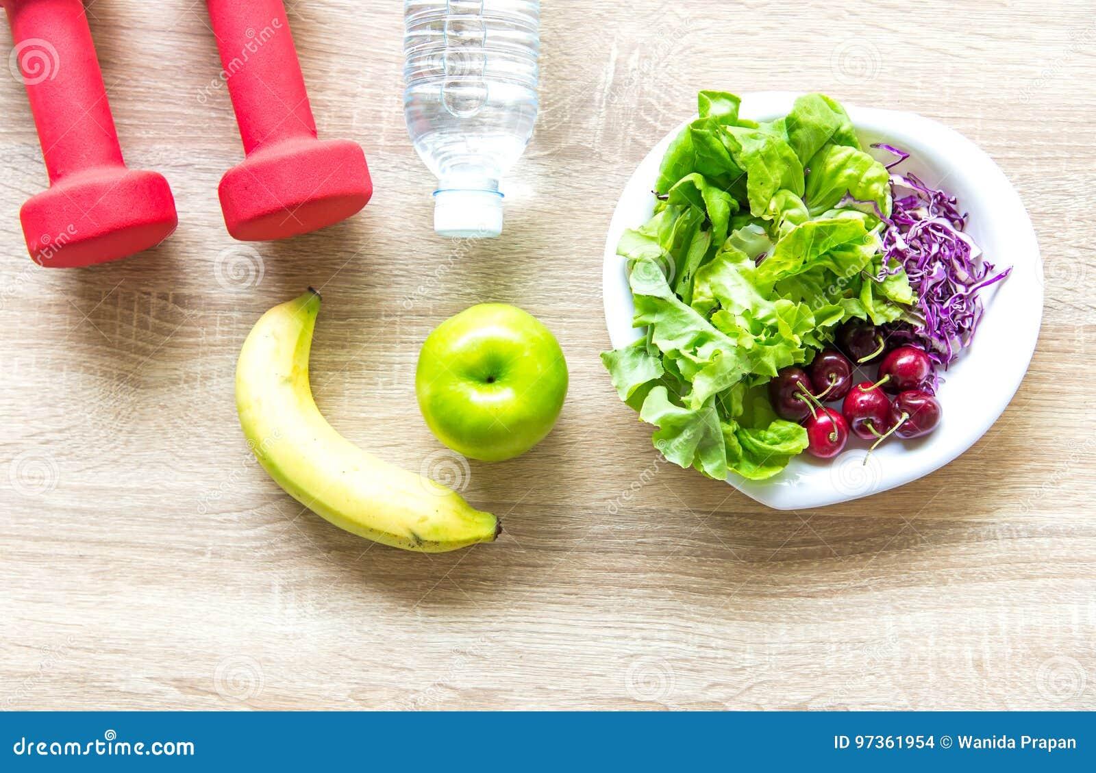 O estilo de vida saudável para mulheres faz dieta com equipamento de esporte, sapatilhas, a fita de medição, as maçãs do fruto e