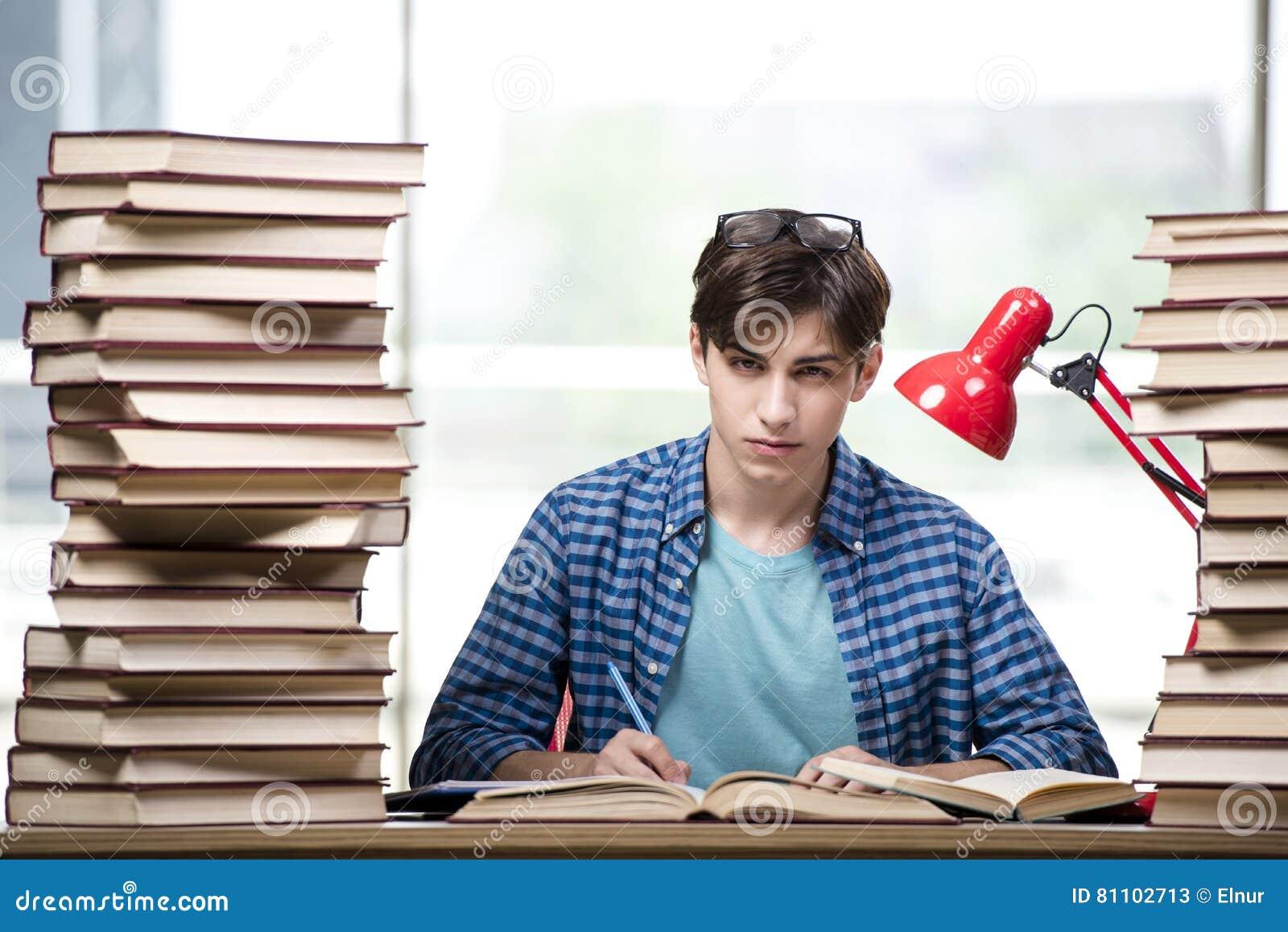 O estudante com lotes dos livros que preparam-se para exames