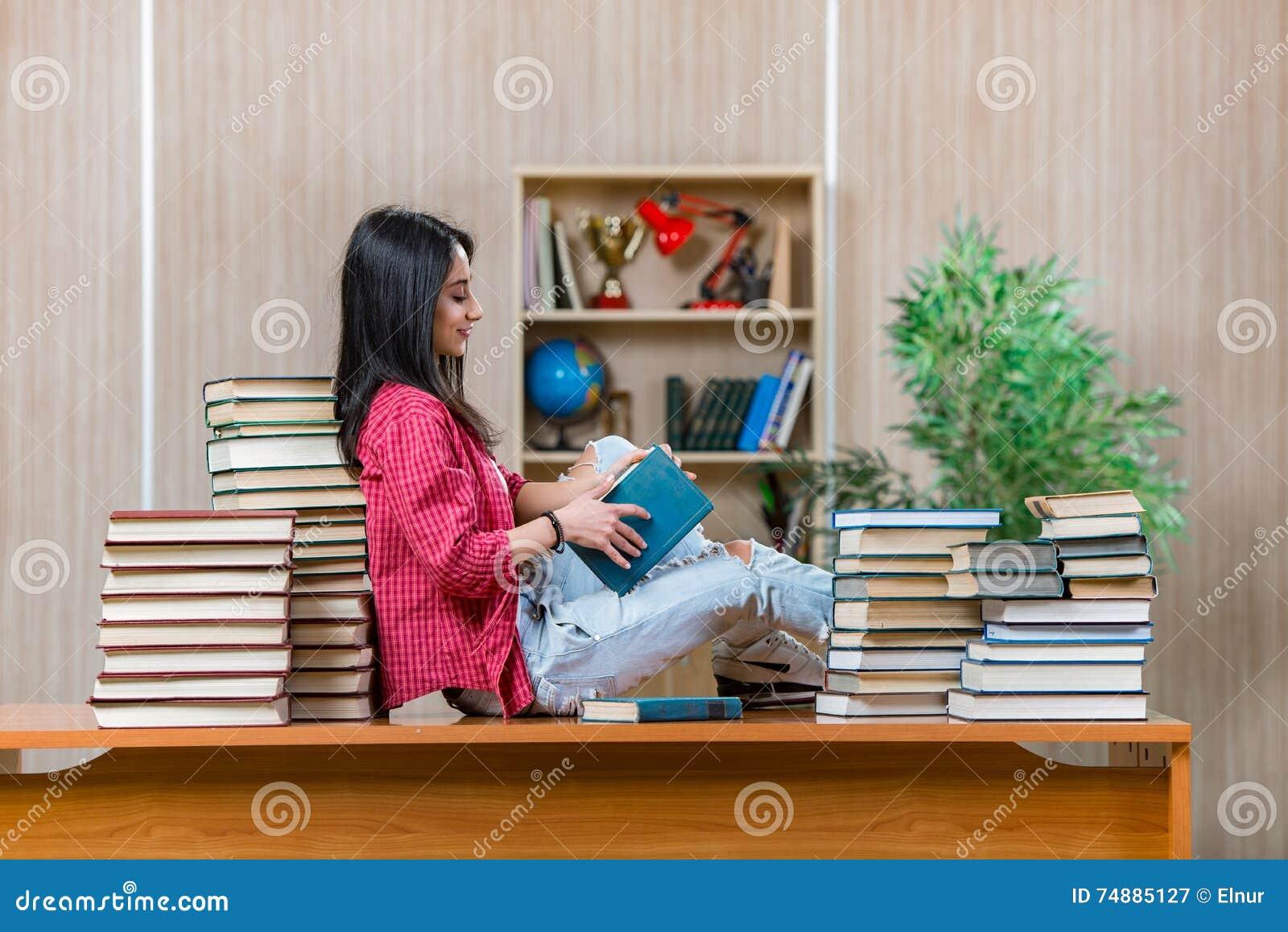 O estudante fêmea novo que prepara-se para exames da escola da faculdade