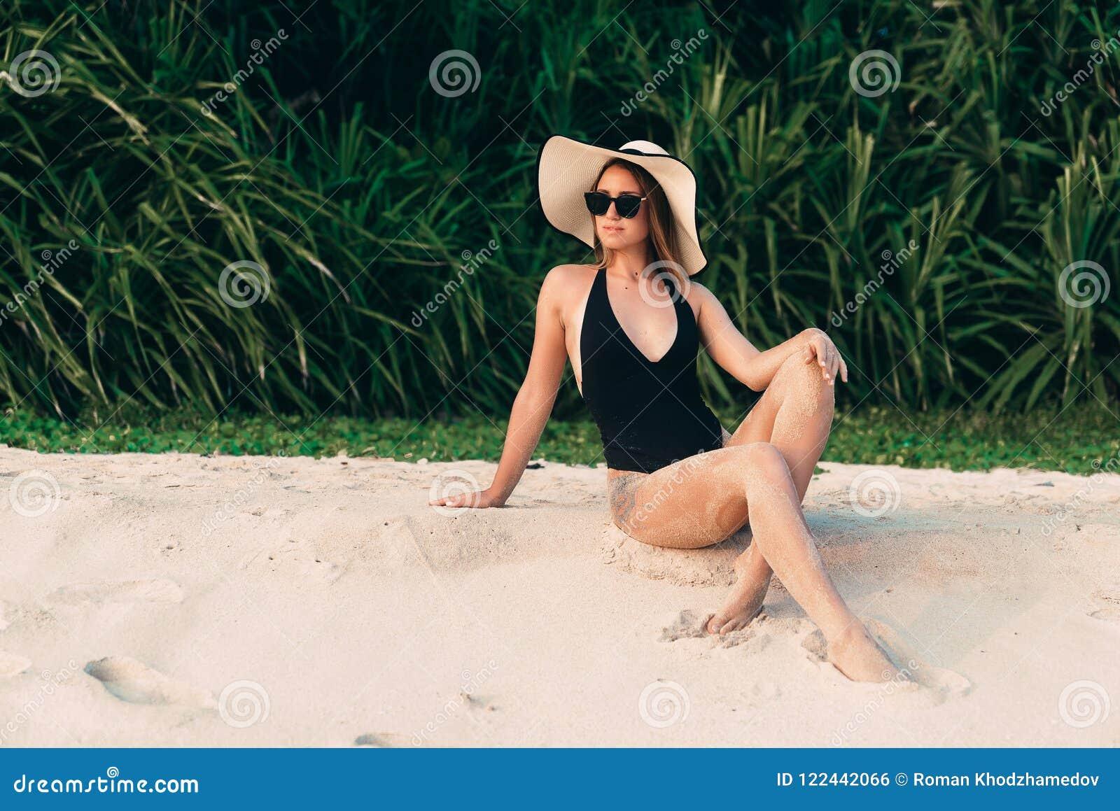 O europeu com pele lisa macia descansa na praia, tomando sol e apreciando o sol, veste um roupa de banho preto à moda, chapéu