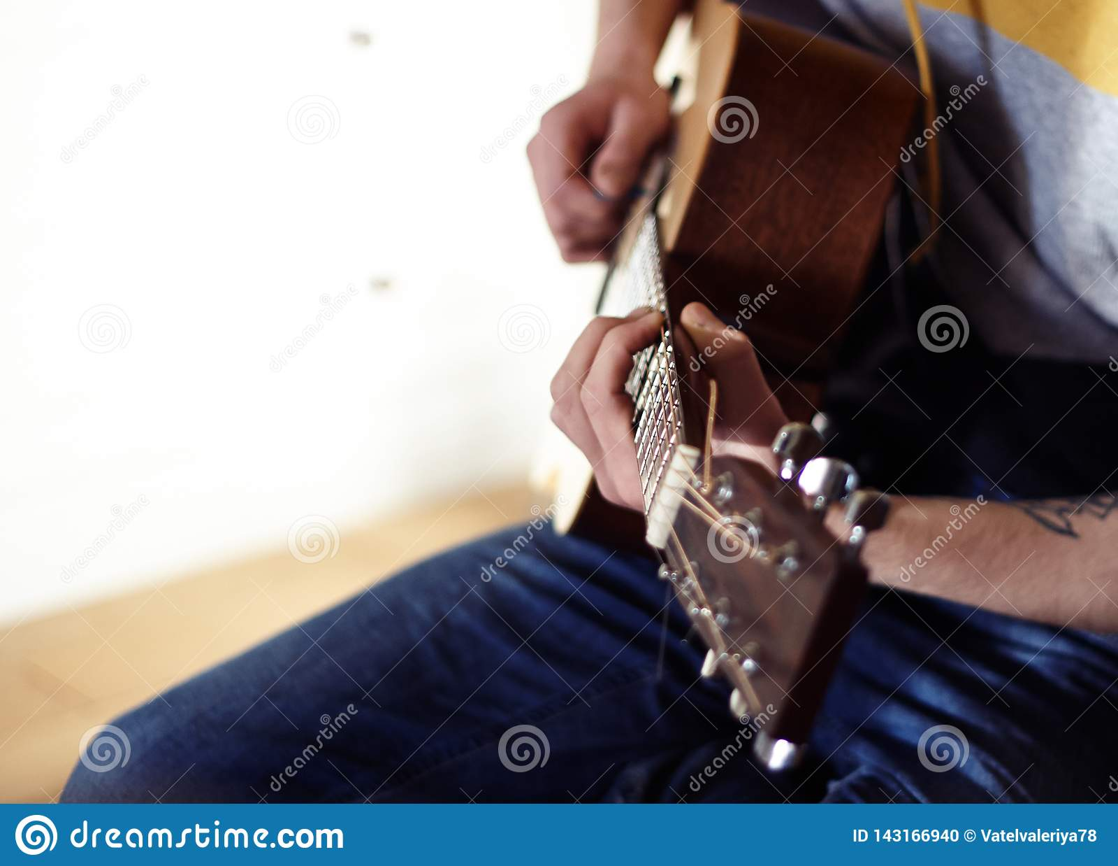O executor joga uma guitarra acústica de madeira