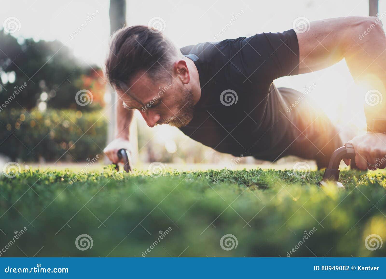 O exercício muscular do atleta empurra acima fora o parque ensolarado Modelo masculino descamisado apto da aptidão no exercício d