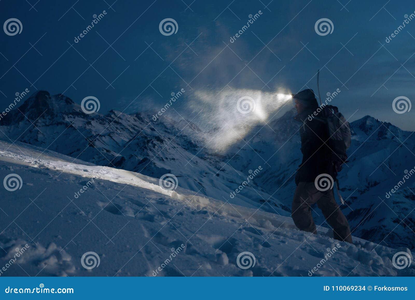 O expeditor profissional comete a escalada em montanhas nevado na noite e nas luzes a maneira com um farol Desgaste vestindo do e