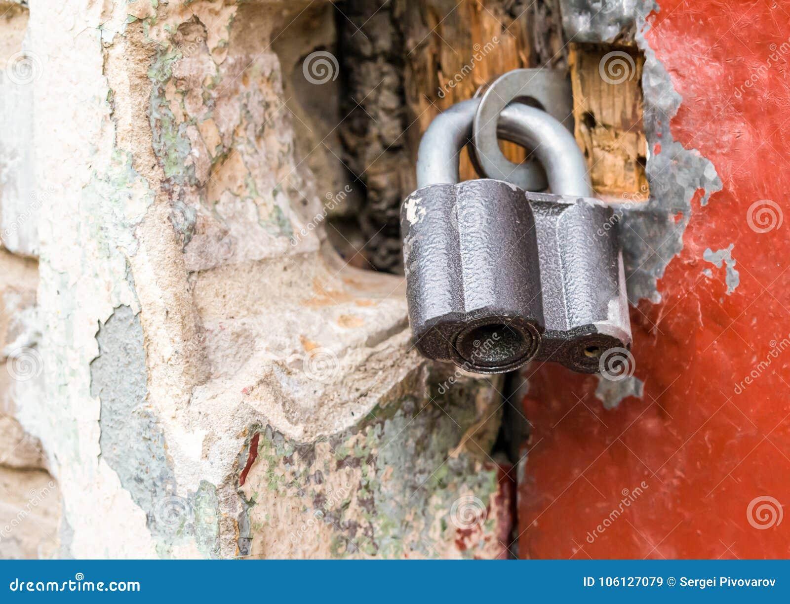 O fechamento grande articulado fecha o close-up da porta contra um fundo quebrado da parede de pedra, fundo do grunge