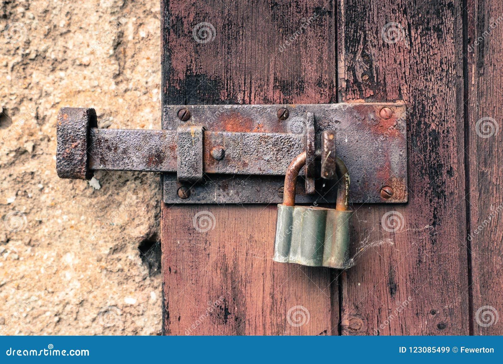 O fechamento oxidado velho fechado e o vintage do ferro padlock em rachar e em descascar a porta de madeira vermelha resistida