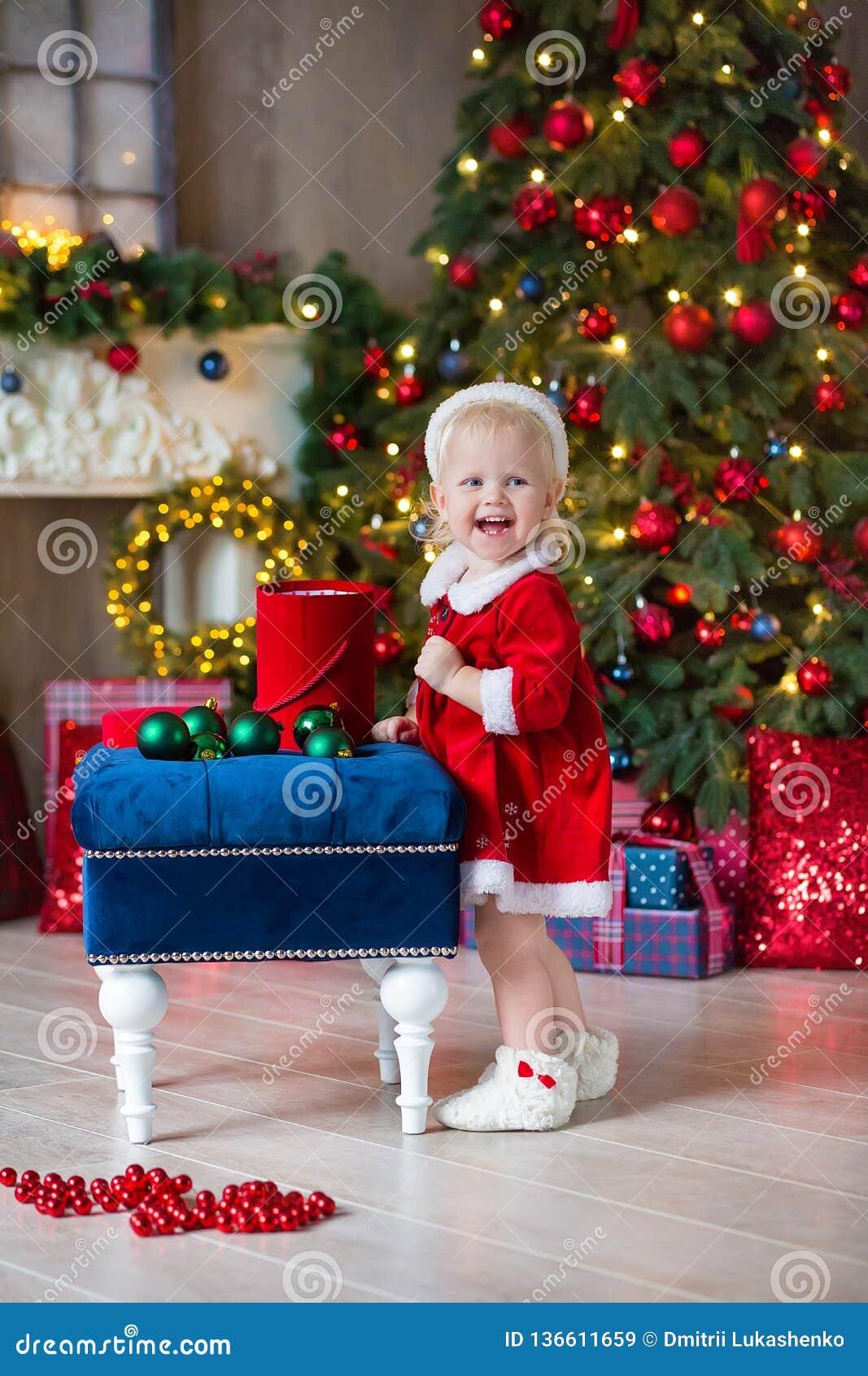O Feliz Natal e boas festas menina bonito da criança pequena está decorando a árvore de Natal dentro
