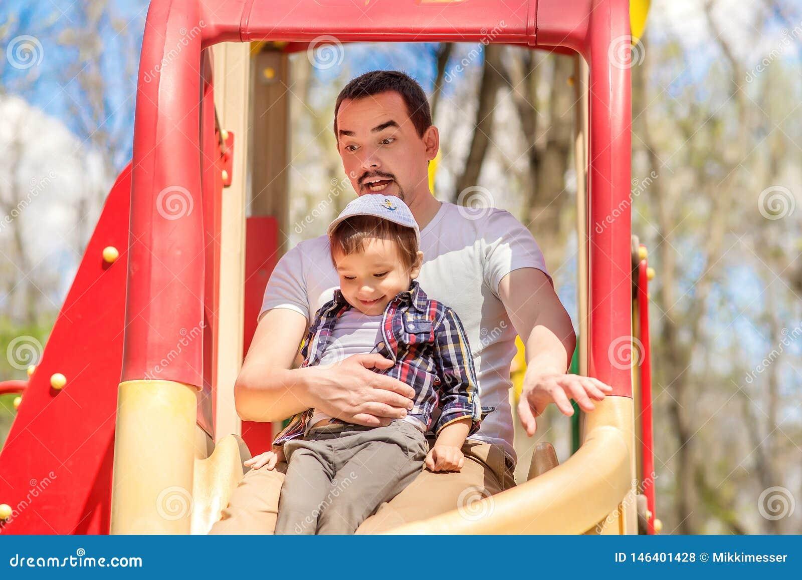 O filho do pai e da criança que desliza das crianças desliza no parque A criança está sentando-se em joelhos do paizinho, pai é e