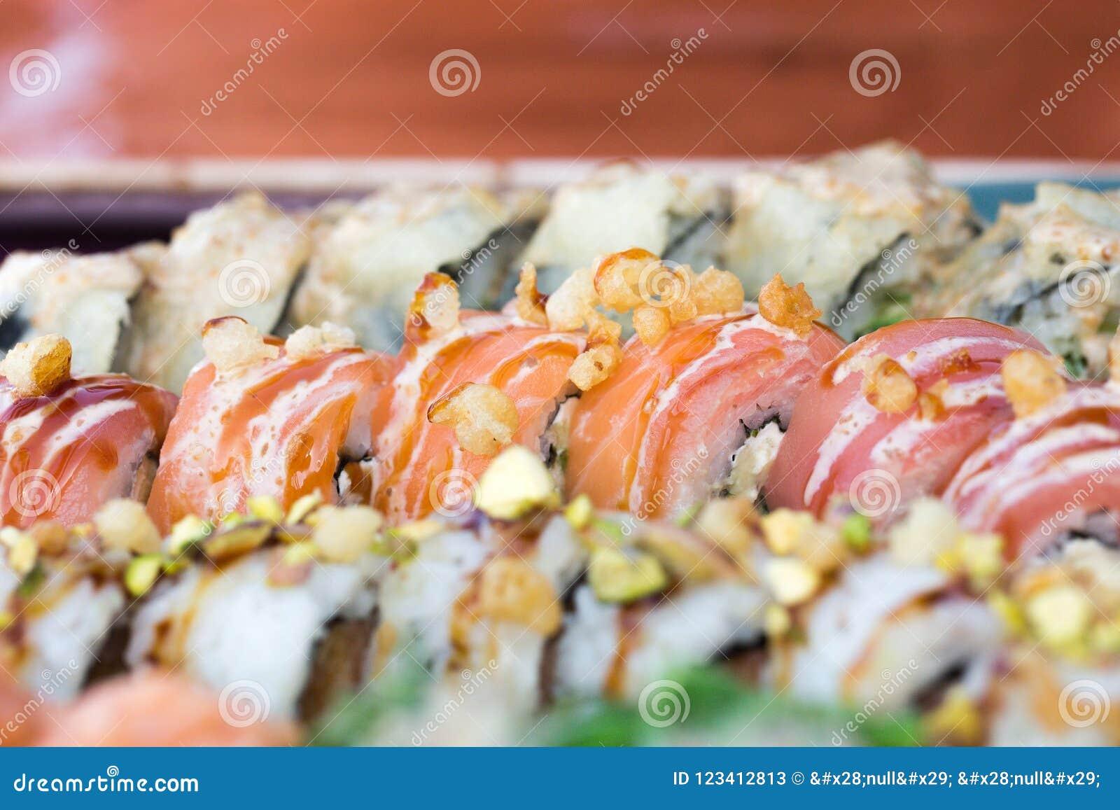 O fim acima da imagem do alimento do grupo do sushi serviu no fundo cerâmico da placa Foto para elementos do texto e do projeto