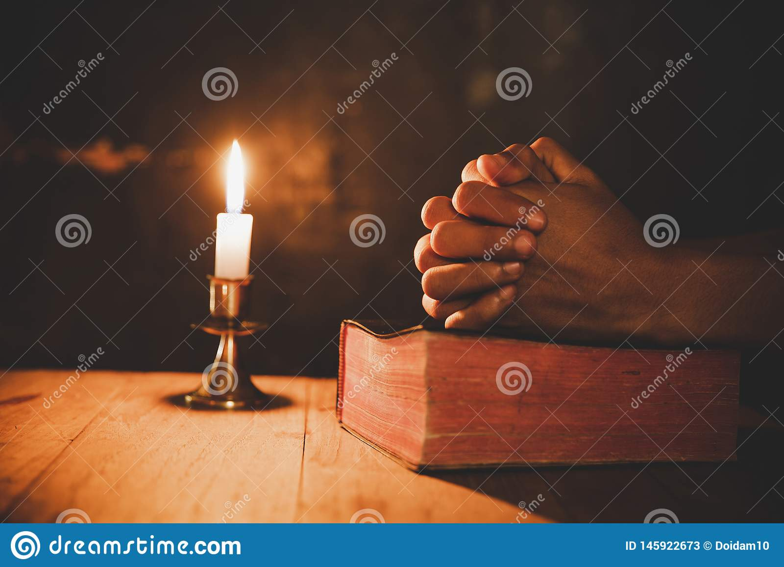 O fim acima da mão do homem está rezando na igreja com vela iluminada