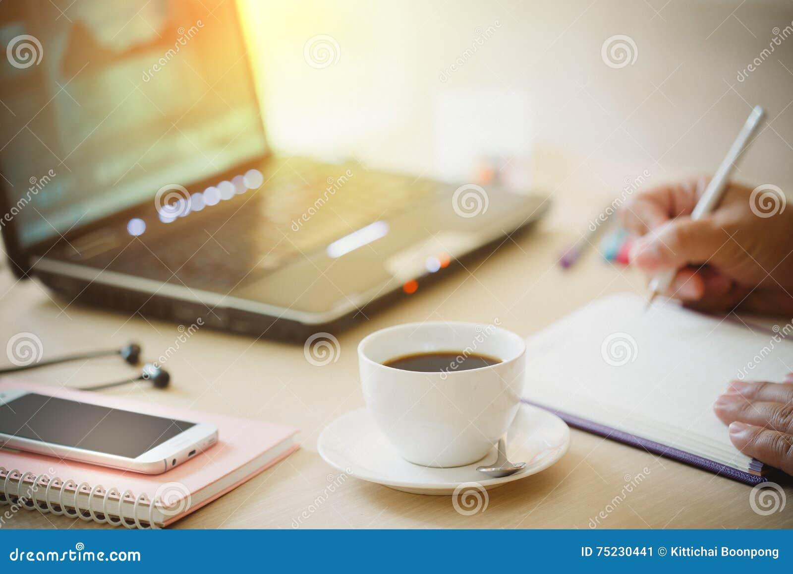 O fim acima da xícara de café e o telefone esperto com mão do homem de negócio que usa o laptop e escrevem o caderno no escritóri