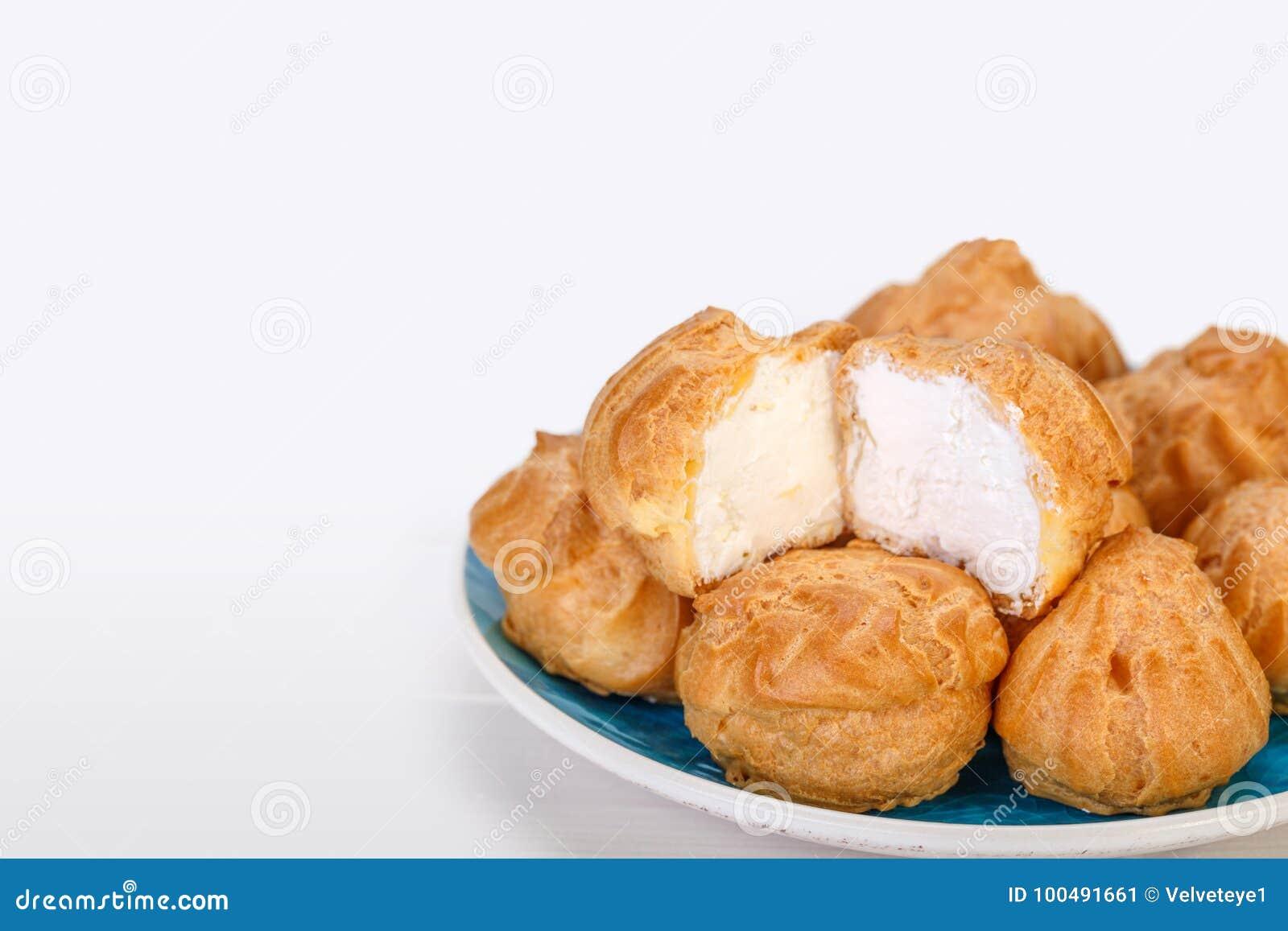 O fim acima de bolos frescos dos sopros de creme de Profiteroles encheu-se com o pas
