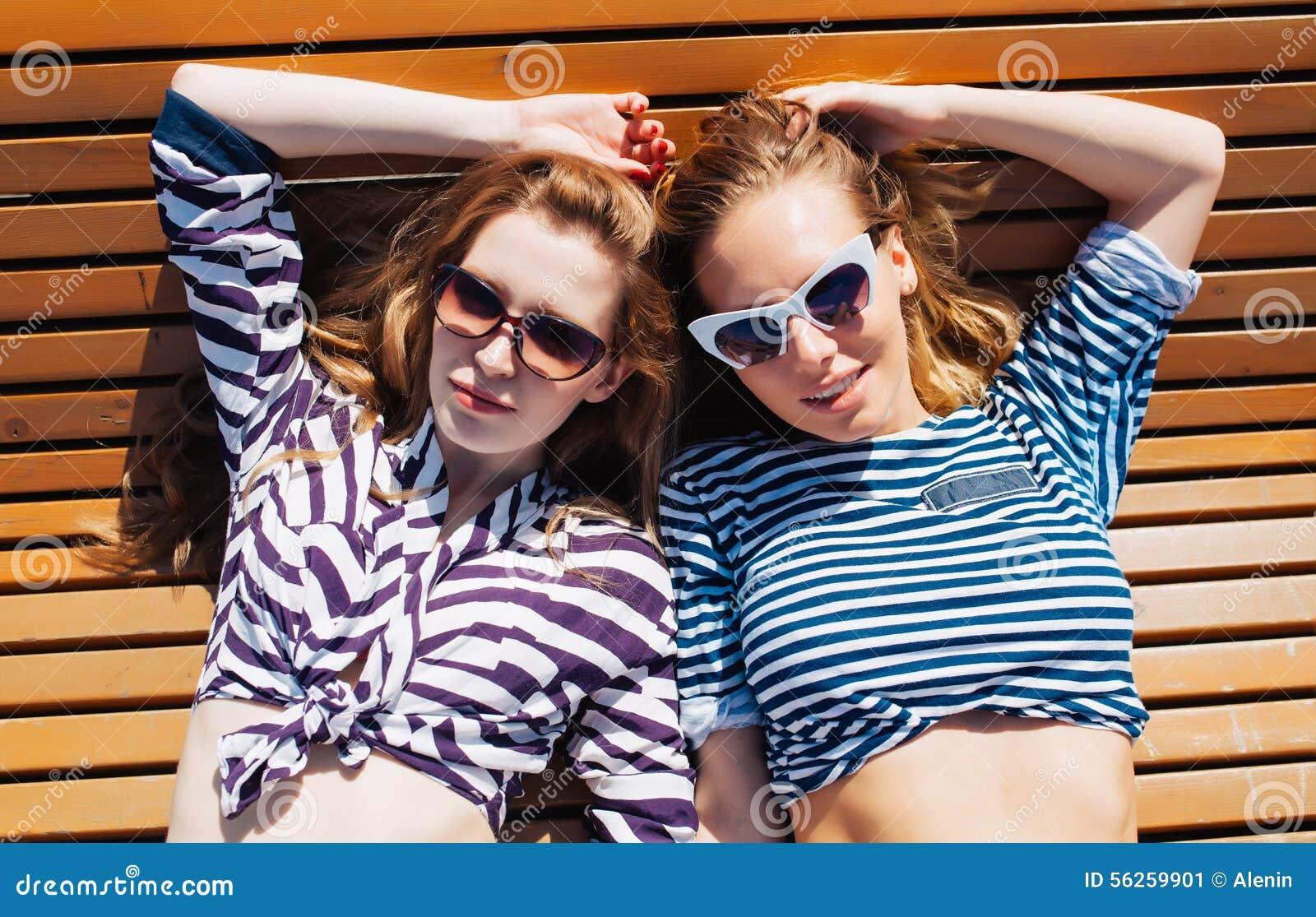 O fim acima de um retrato do verão do estilo de vida de dois amigos de meninas relaxado e que obtêm toma sol, colocando na praia,