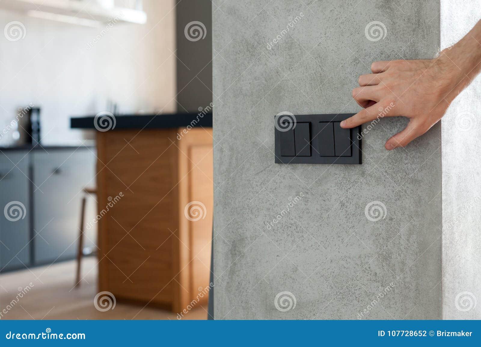O fim acima do dedo está girando de ligar/desligar no interruptor da luz Copie o espaço
