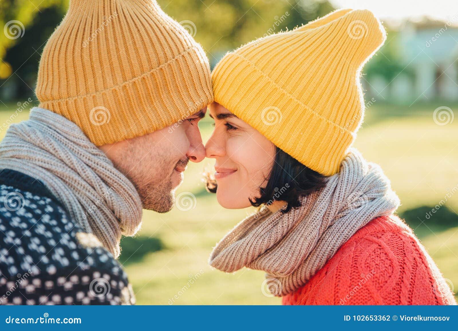 O fim acima do retrato de pares bonitos veste chapéus mornos e olhar do lenço com os olhos completos da felicidade e da apreciaçã