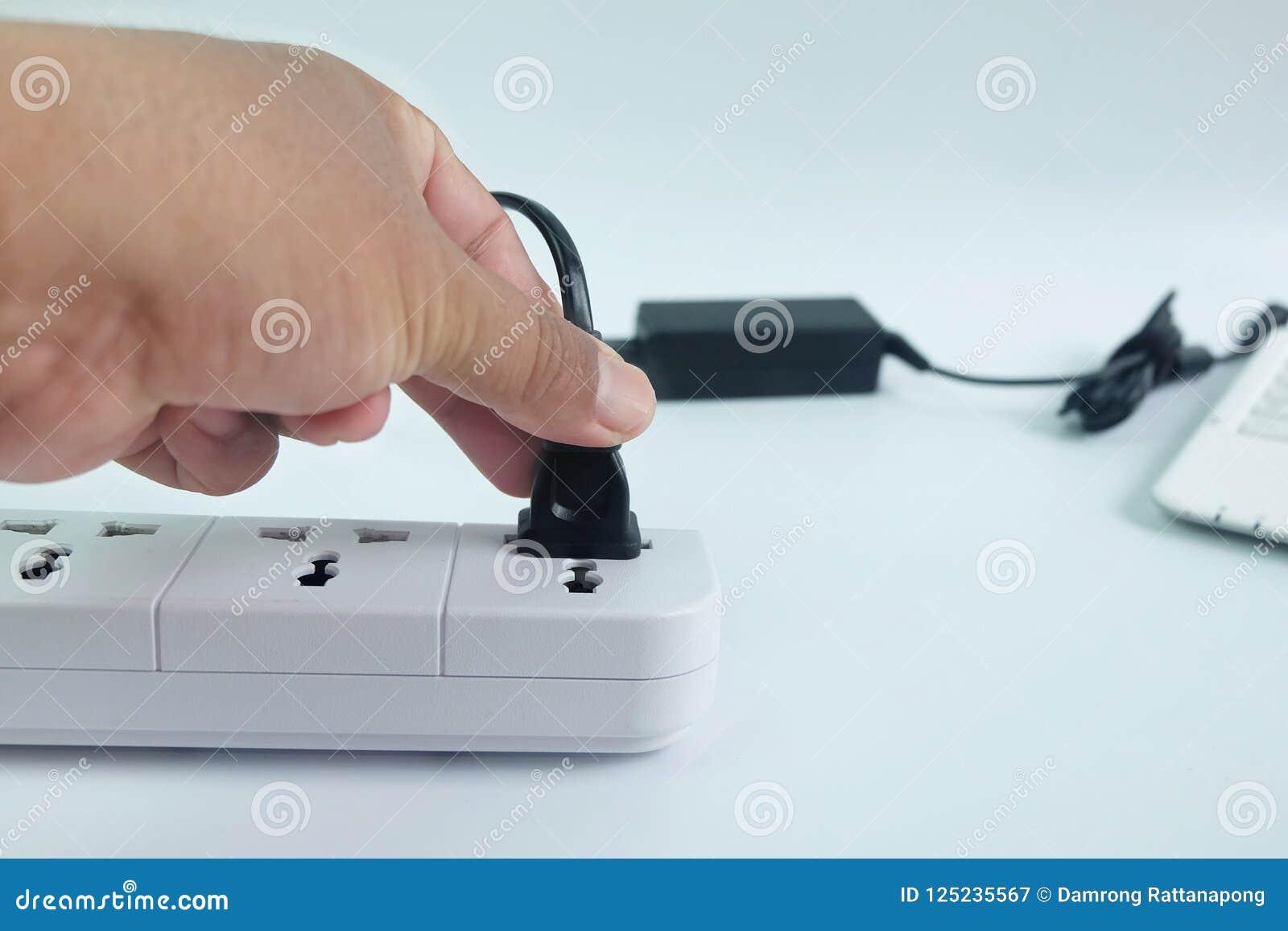 O fim acima dos homens as mãos do ` s que são obstrui dentro o carregador do cabo de alimentação do adaptador com o laptop borrad