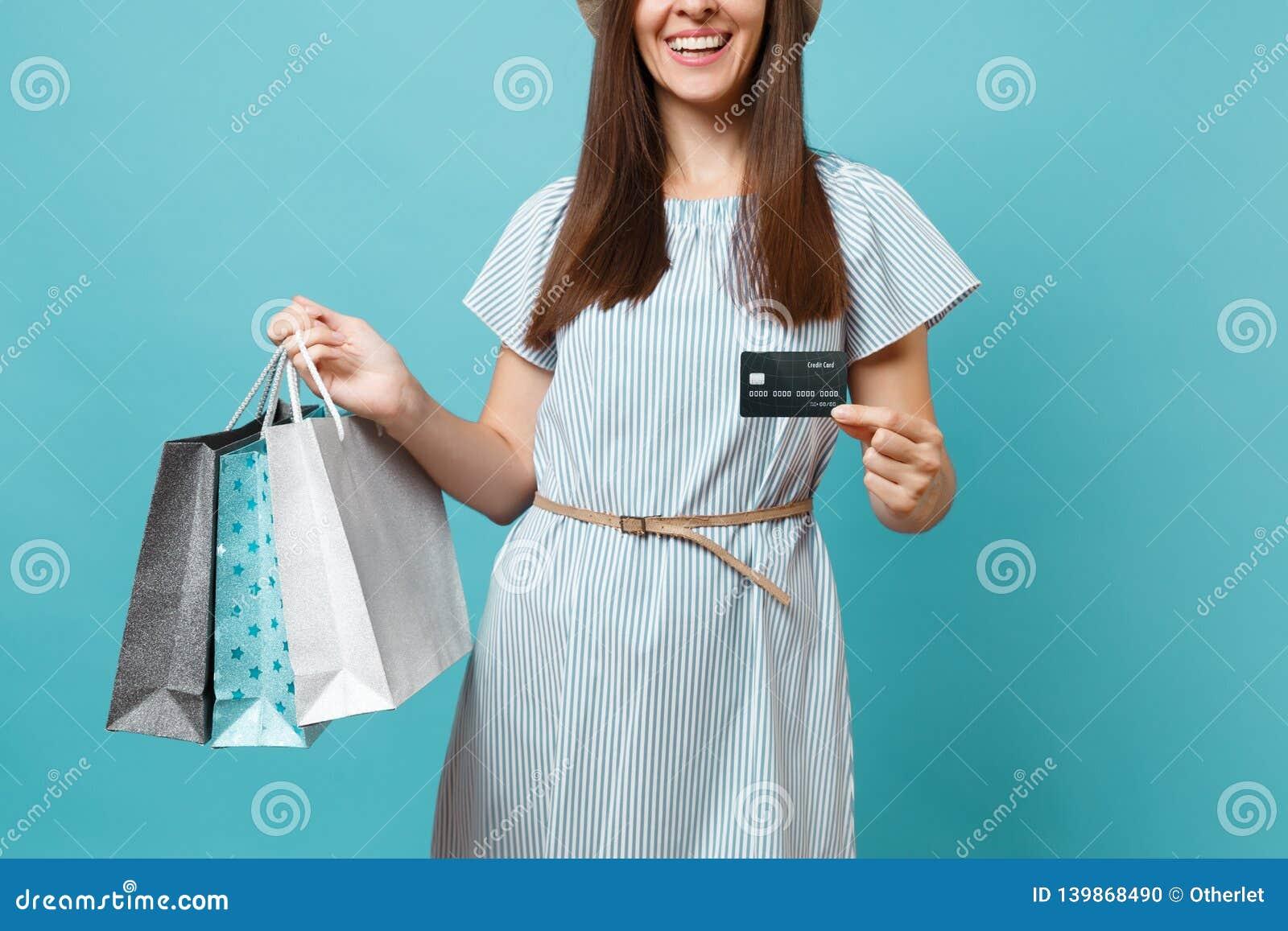 O fim colheu acima a mulher caucasiano bonita de sorriso no vestido do verão que guarda sacos dos pacotes com compras após a comp