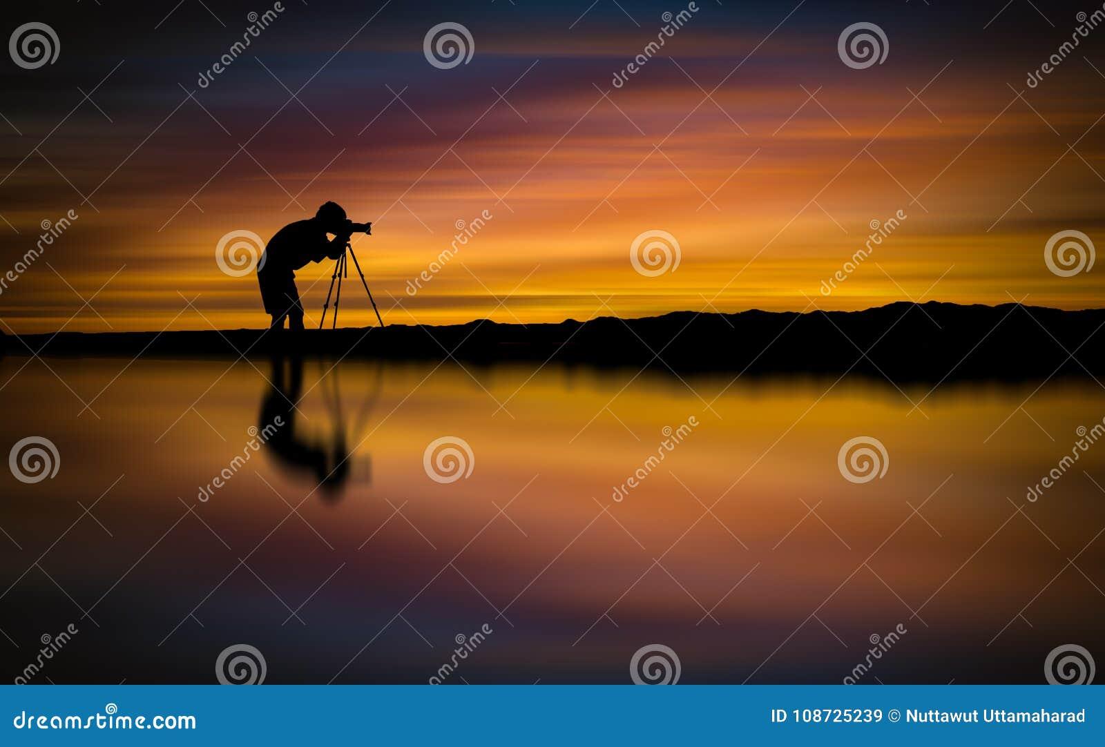 O fotógrafo da silhueta toma a foto o seascape bonito no por do sol
