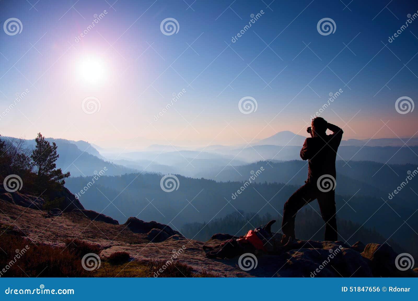 O fotógrafo profissional toma fotos com a câmera do espelho no pico da rocha A paisagem sonhadora do fogy, salta nascer do sol en