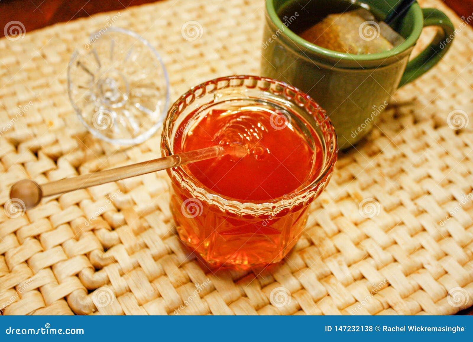 O frasco de vidro aberto com mel e o dipper dourados mergulhou para dentro na esteira de lugar