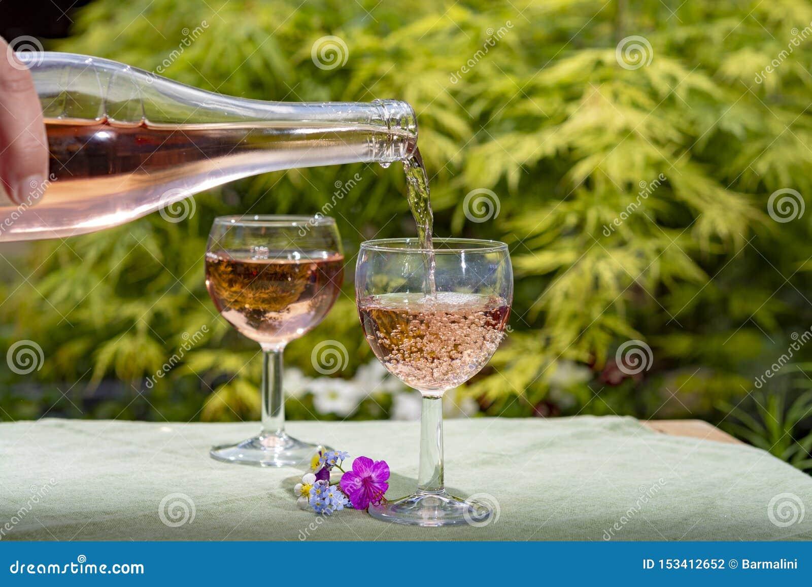 O frio de derramamento do gar?om aumentou vinho nos vidros no dia ensolarado do ver?o no jardim de floresc?ncia