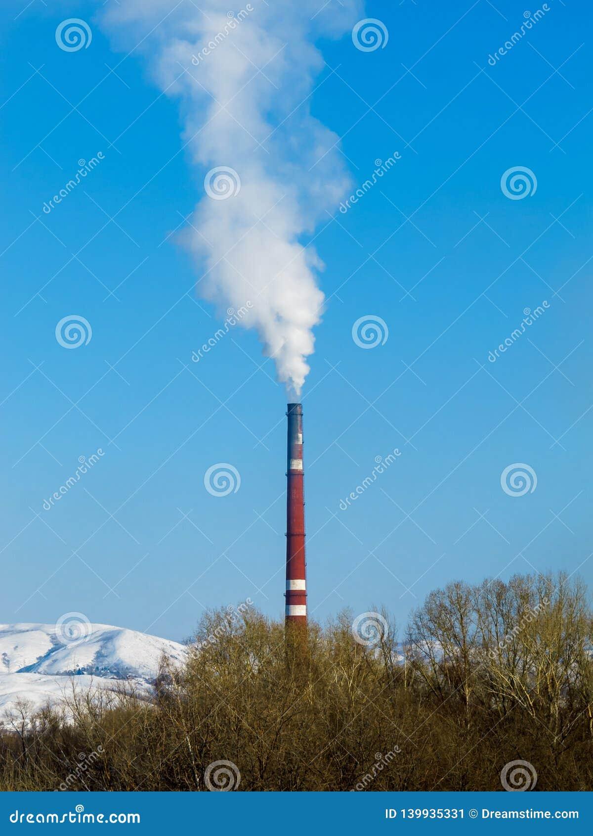 O fumo branco grosso sai da tubulação vermelha da fábrica contra um céu azul claro, umas montanhas nevados e umas copas de árvore
