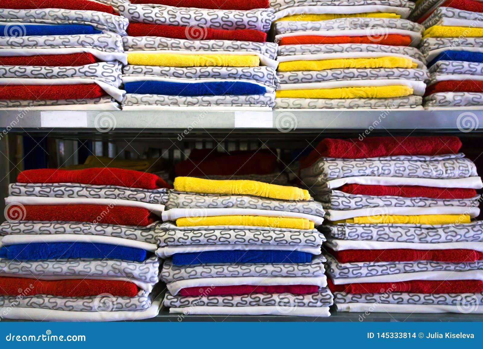O fundamento está no armário na prateleira As toalhas dobraram-se em um rolo Nos ganchos que penduram senhoras e roupa dos home