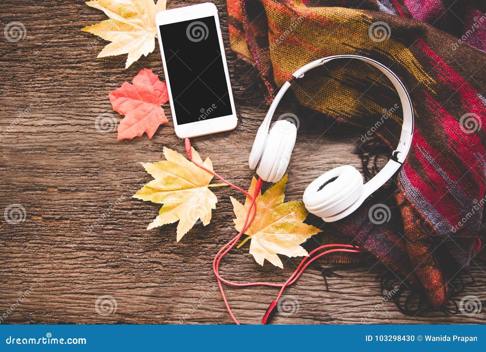 O fundo acolhedor do inverno, o copo do café quente com marshmallow e a música do fones de ouvido, telefone esperto, aquecem a ca
