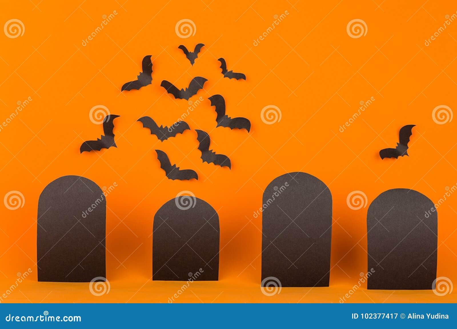 O fundo alaranjado de Dia das Bruxas com etiquetas pretas vazias da venda e os bastões reunem-se, zombam-se acima