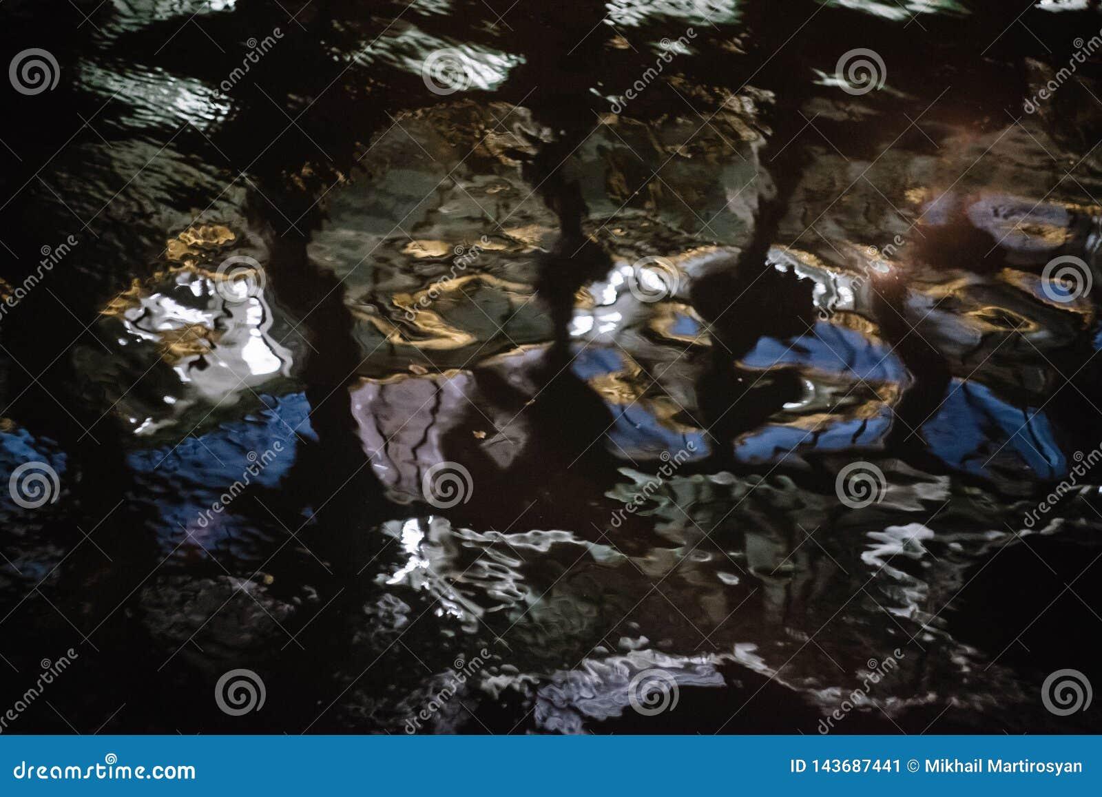 O fundo borrou a textura da água na noite Destaques da cor na água Pode ser usado como um fundo para o texto ou um backgroundon