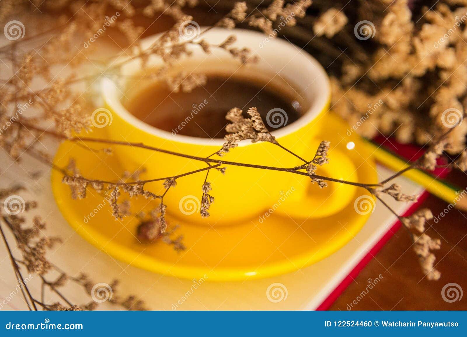 O fundo claro obscuro do projeto do copo de café cerâmico amarelo pôs na parte traseira do estilo secado da flor, do vintage e da