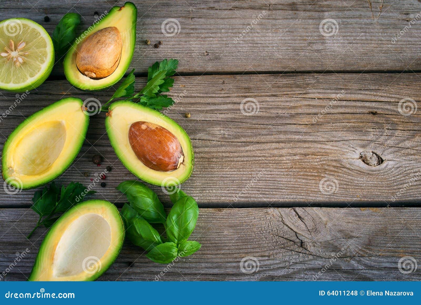 O fundo do alimento com abacate, o cal, a salsa e a manjericão em velho cortejam
