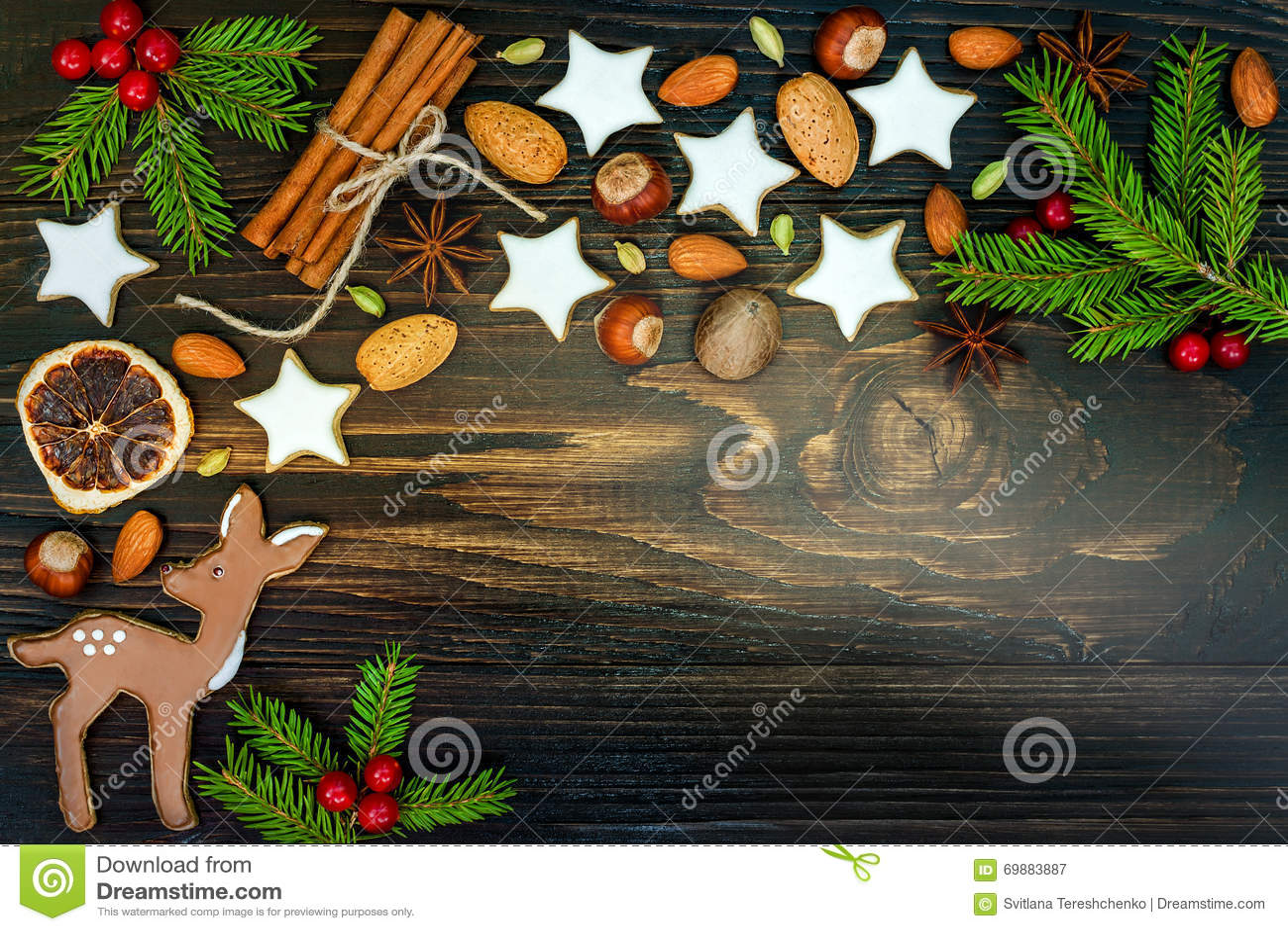 O fundo do feriado do Natal com cookies e abeto do pão-de-espécie ramifica na placa de madeira velha Copie o espaço