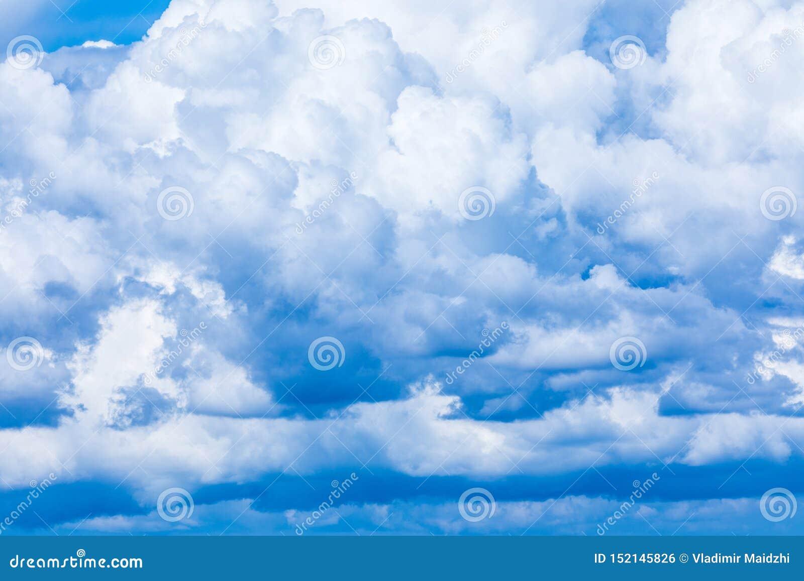 O fundo vívido do céu ou do céu com as nuvens brancas sob os raios do sol