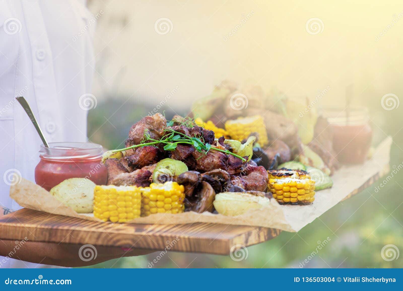 O garçom está oferecendo a carne e vegetais grelhados no dia ensolarado
