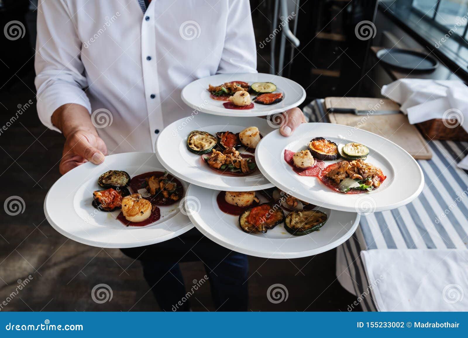 O garçom serve antipasti italianos em um restaurante exterior