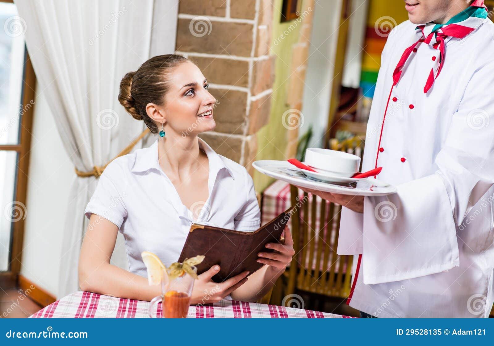 O garçom traz um prato para uma mulher agradável