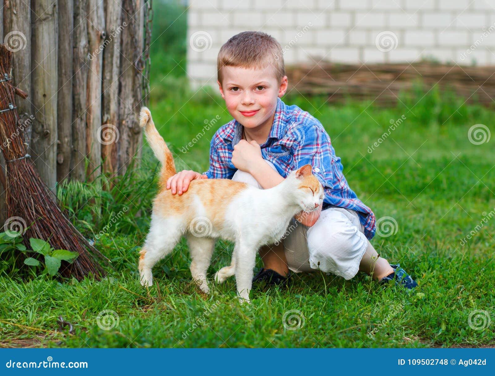 O gato vermelho fricciona maciamente contra a mão de um rapaz pequeno