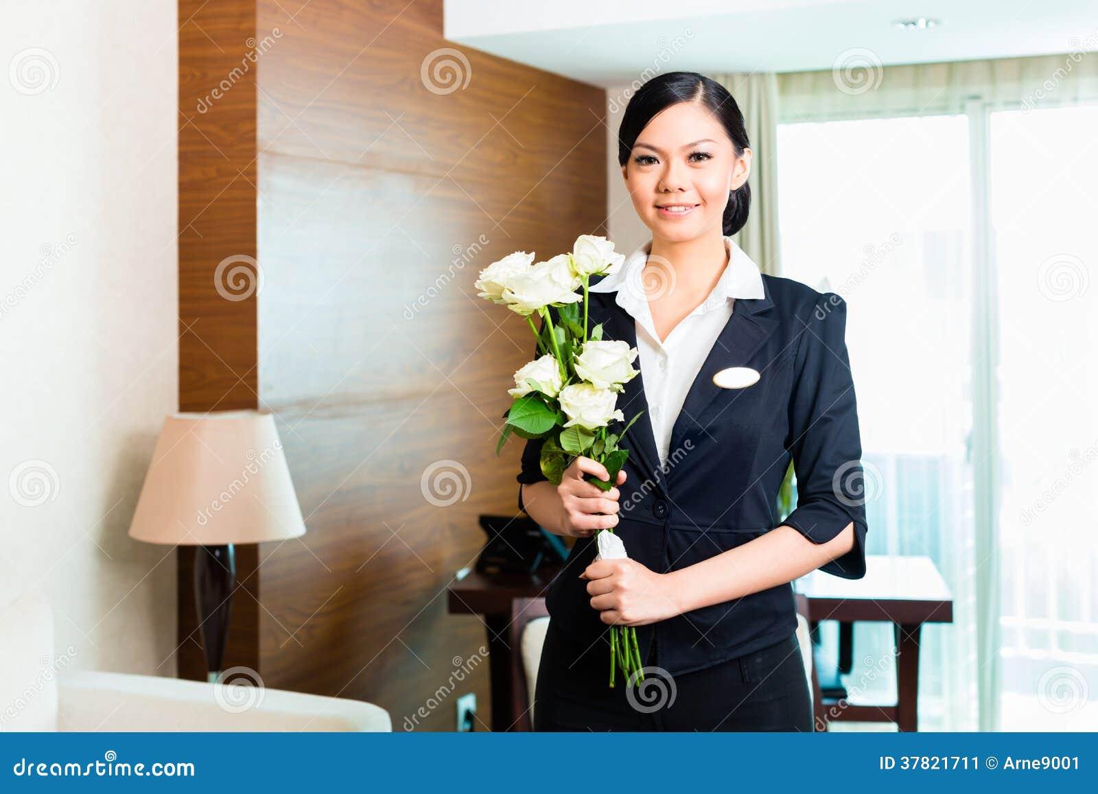 O gerente de hotel chinês asiático dá boas-vindas a convidados de chegada do VIP