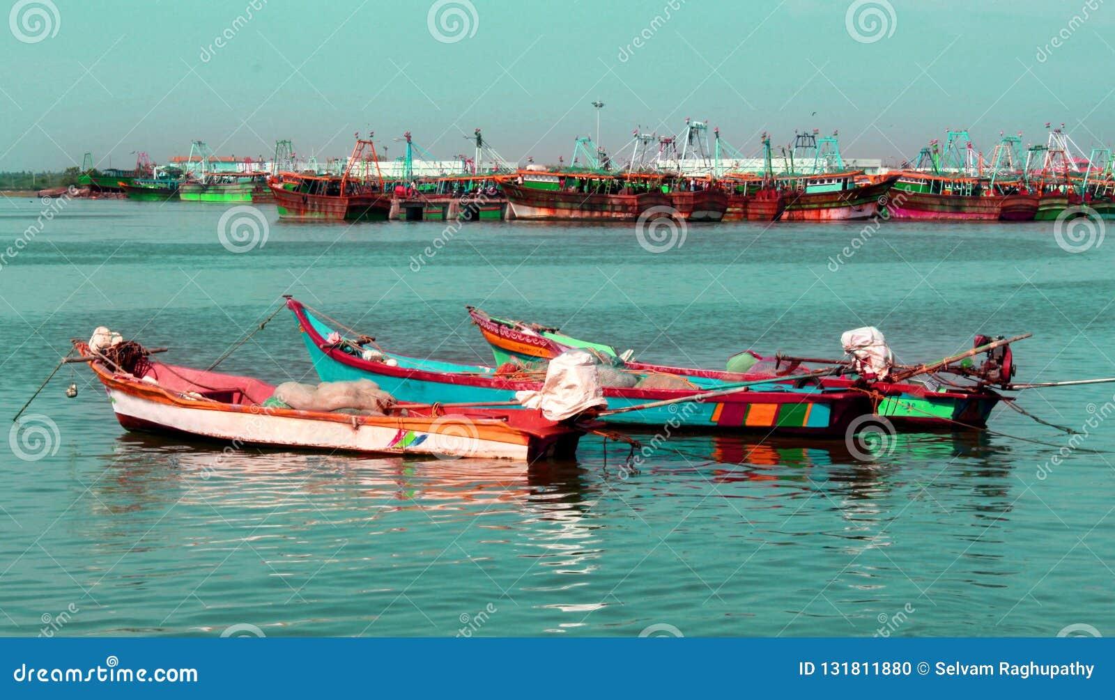 O grande e os botes estacionados no arasalaru do rio para aprontar-se para travar peixes