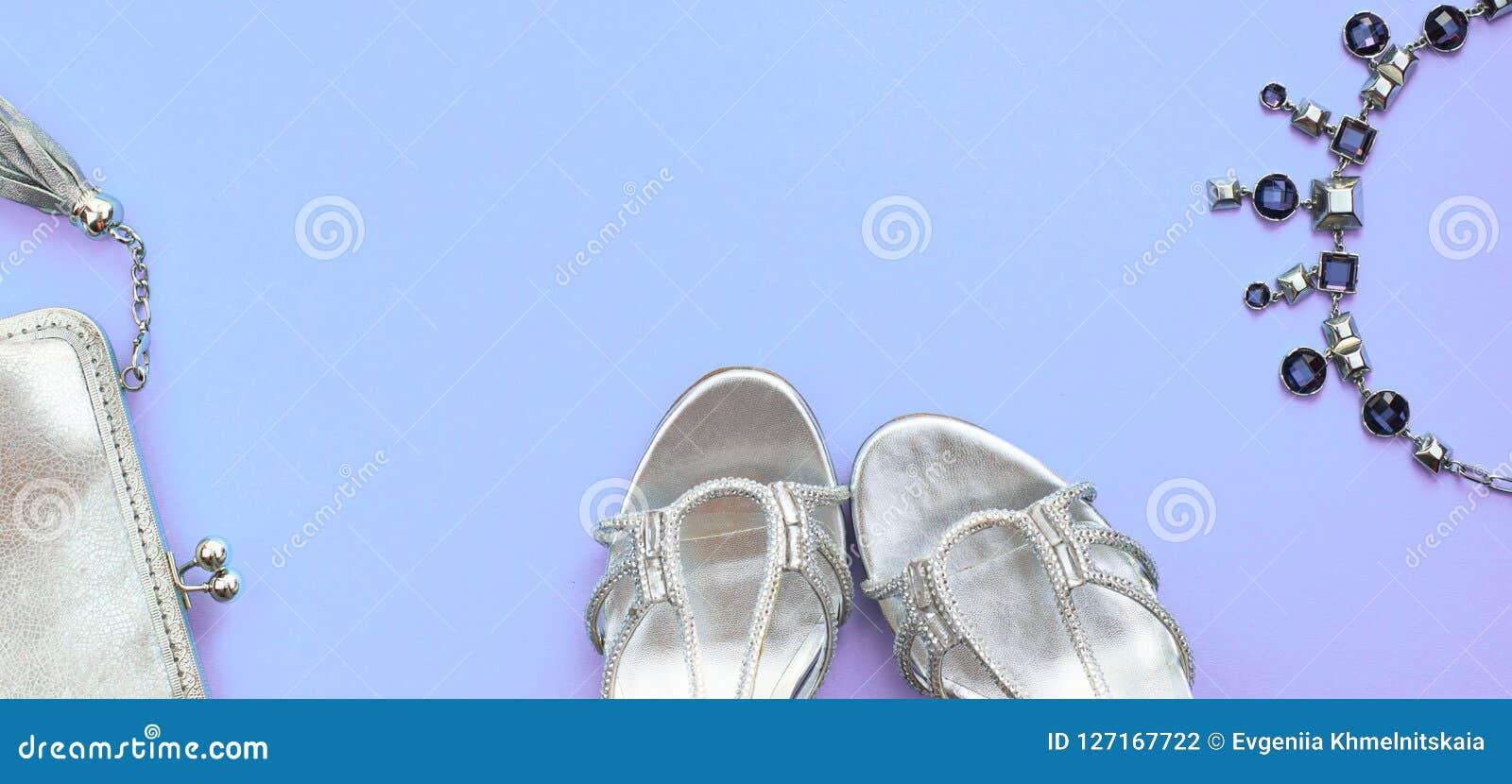 O grupo da bandeira de plano dos acessórios de forma coloca a cor da prata da joia da colar da bolsa das sapatas no espaço roxo d