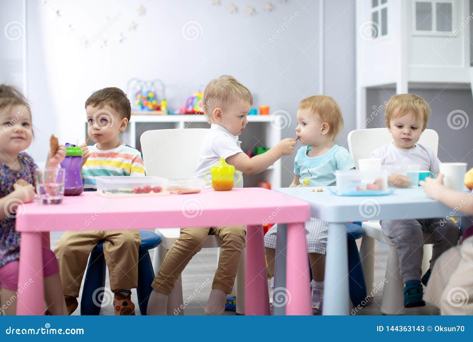 O grupo das crianças tem o almoço no jardim de infância Menino bonito da criança que compartilha de uma menina da refeição