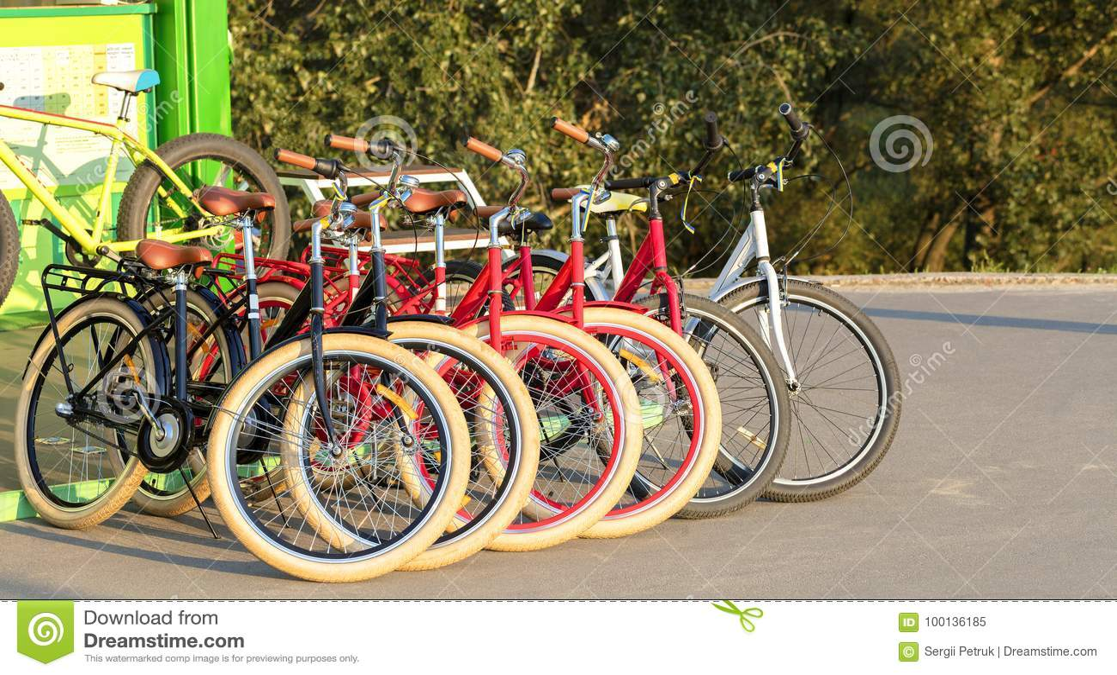 O grupo de bicicletas coloridas estacionou junto em um close up do parque de estacionamento