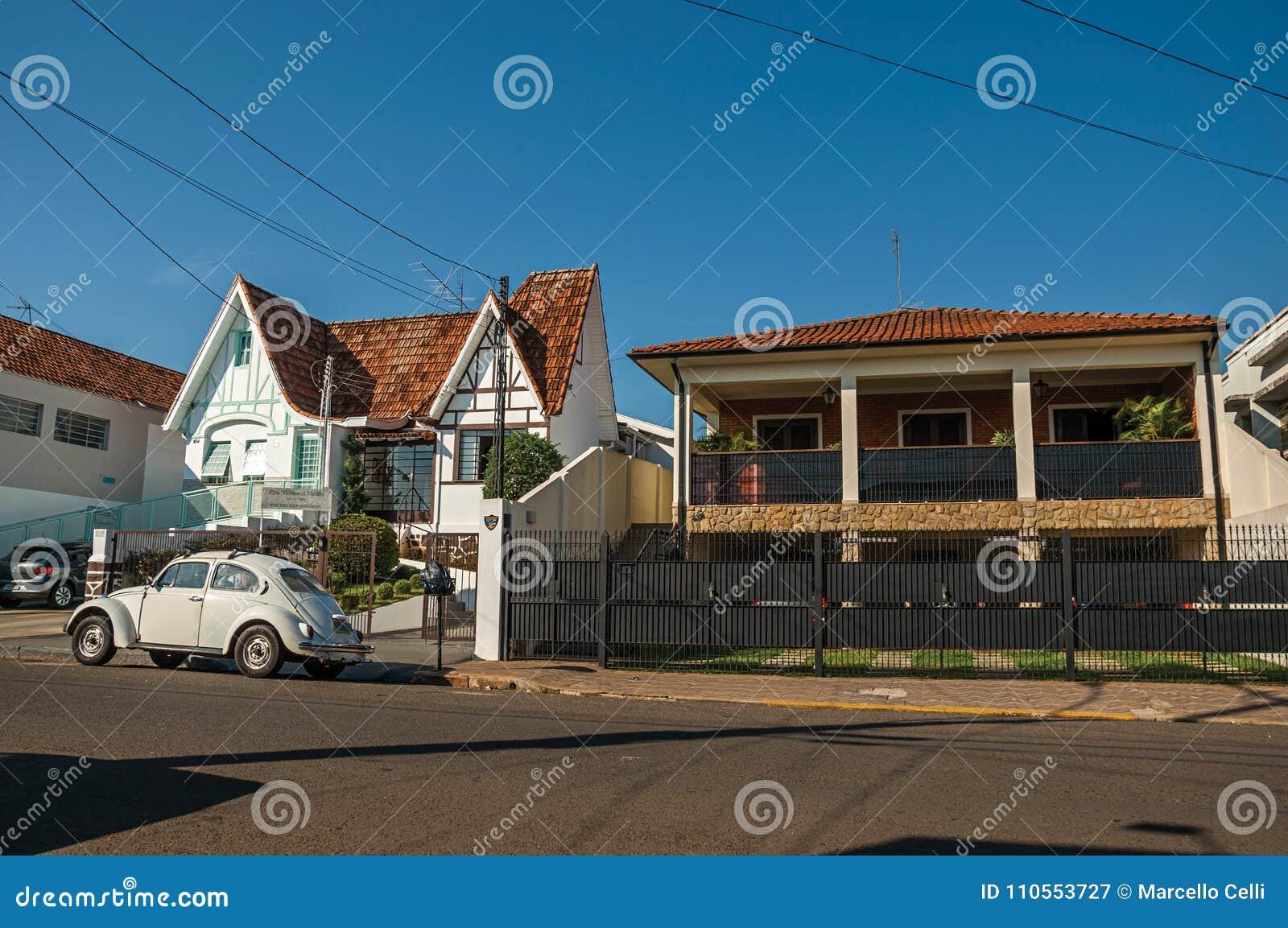 O grupo de casas na rua quieta com um carro do besouro estacionou na parte dianteira, em um dia ensolarado em São Manuel