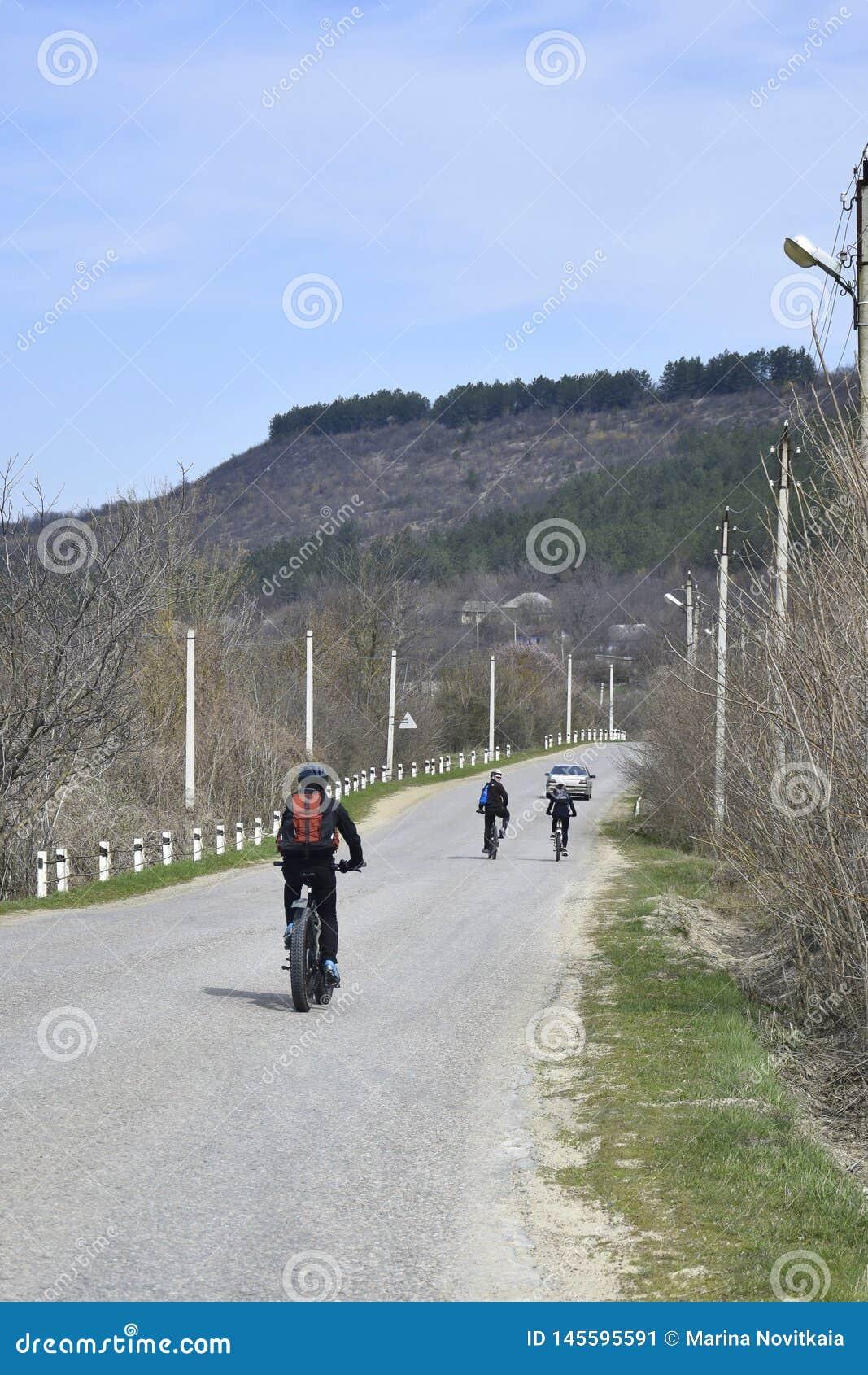 O grupo de ciclistas novos est? conduzindo ao longo de uma estrada asfaltada