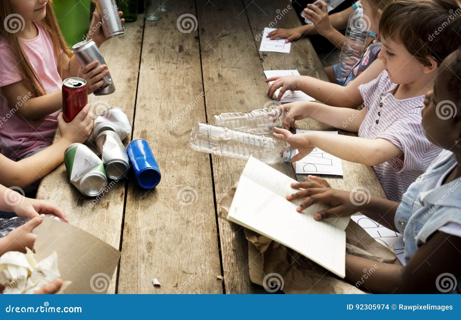 O grupo de colegas das crianças que aprendem a biologia recicla o ambiente