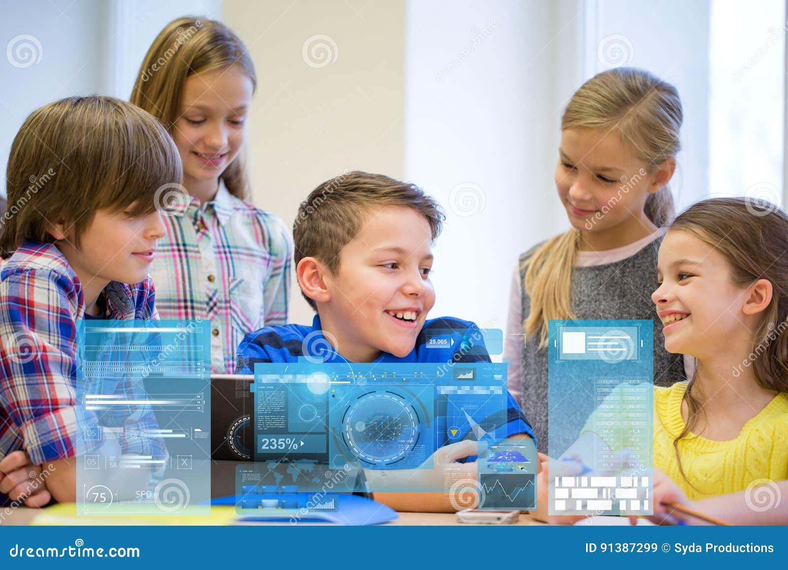 O grupo de escola caçoa com o PC da tabuleta na sala de aula
