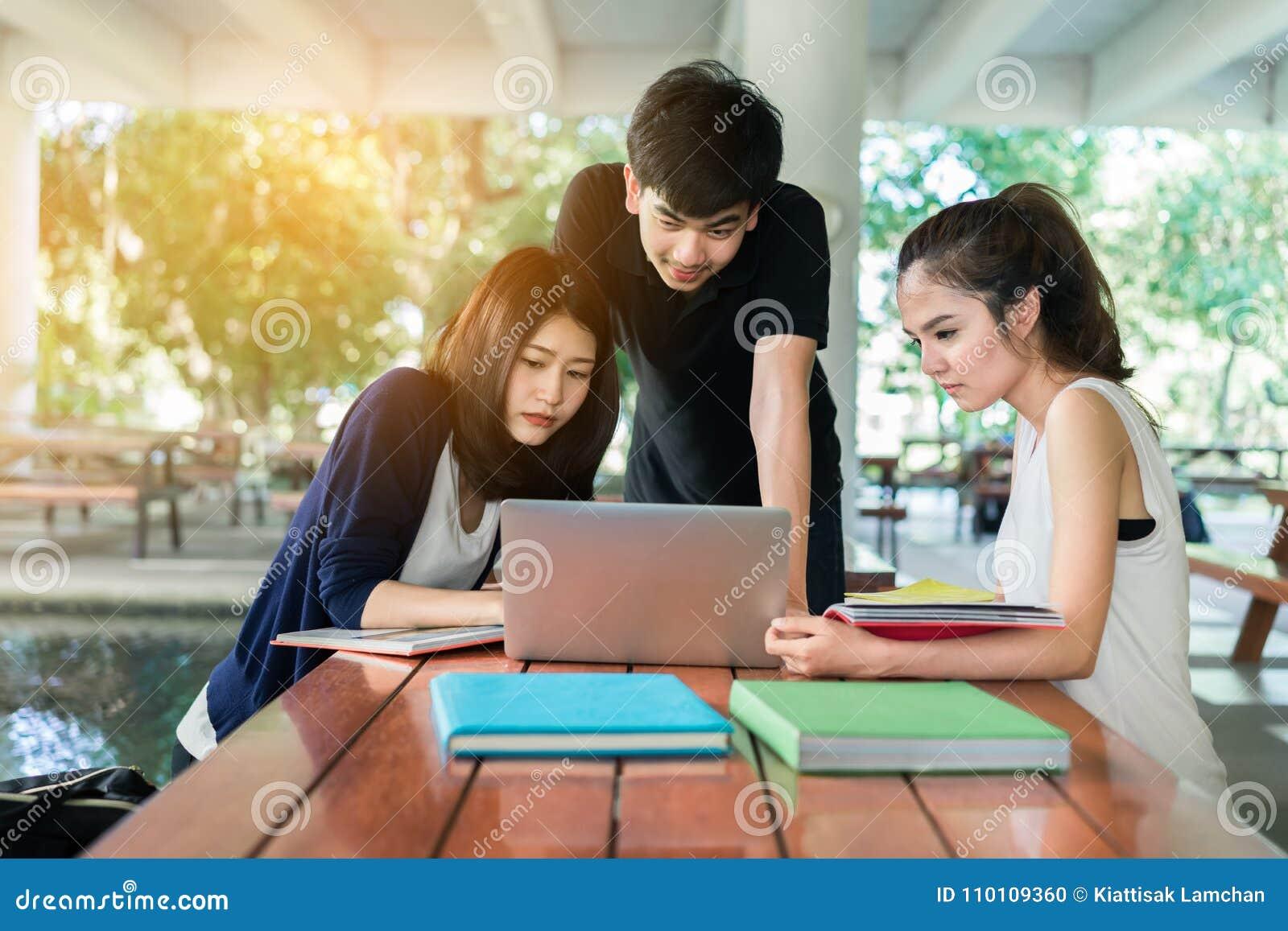 O grupo de estudantes novo consulta com os dobradores da escola, laptop
