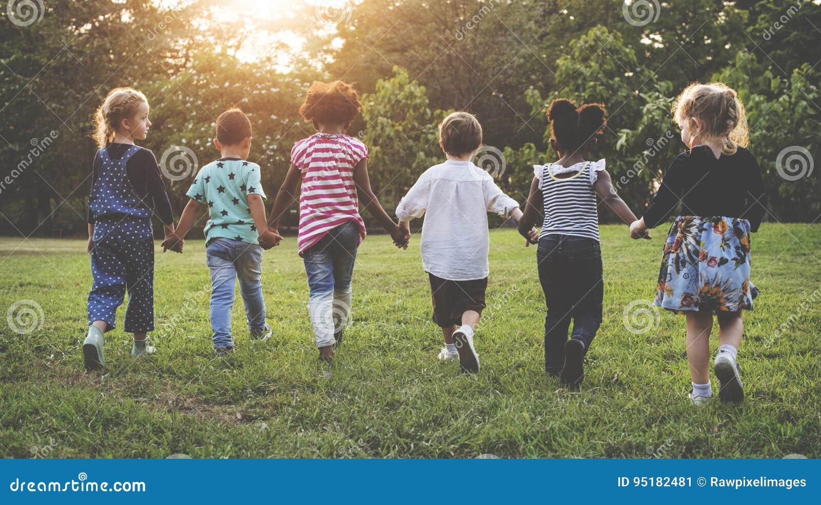 O grupo de jardim de infância caçoa os amigos que guardam as mãos que jogam no parque