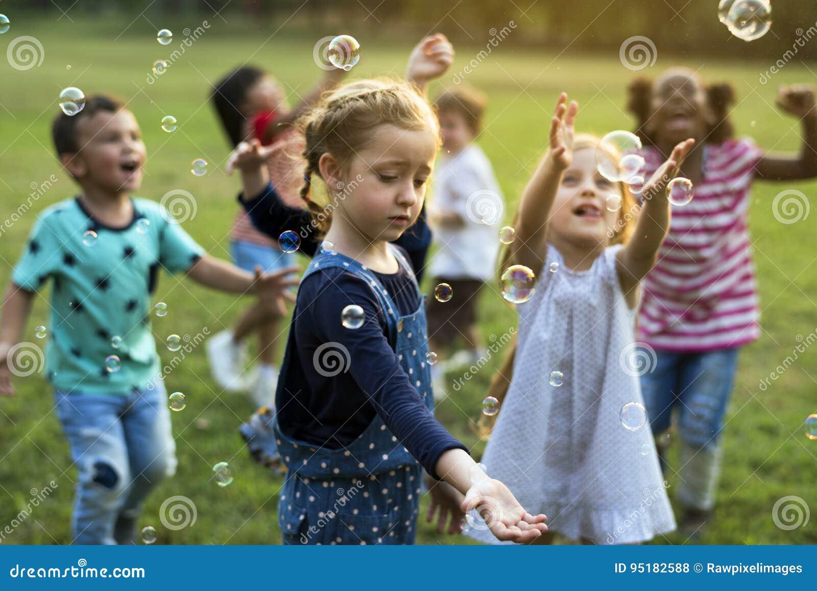 O grupo de jardim de infância caçoa os amigos que jogam o divertimento de sopro das bolhas